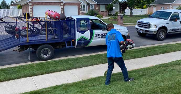 Tuxedo Yard Care employee edging a lawn in Kaysville, Utah